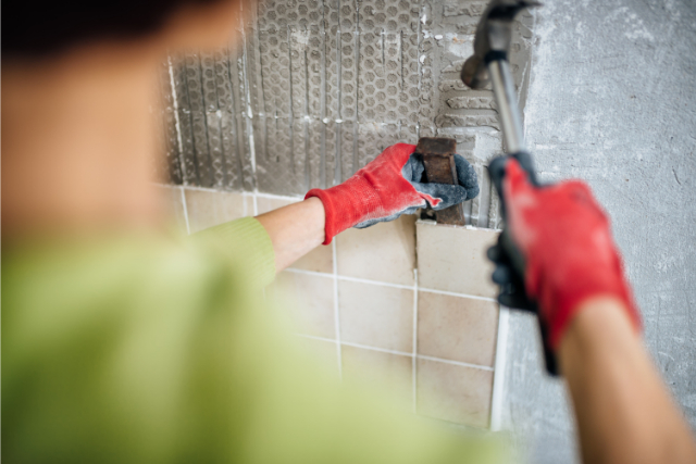 Hillsboro Tile Replacement by worker in Hillsboro with a hammer and chisel
