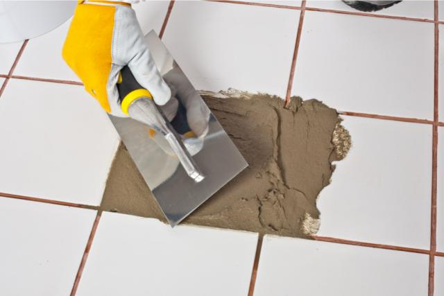 Tile Repair by worker applying grout